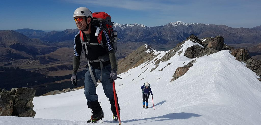 man ascending ridge on alpine course